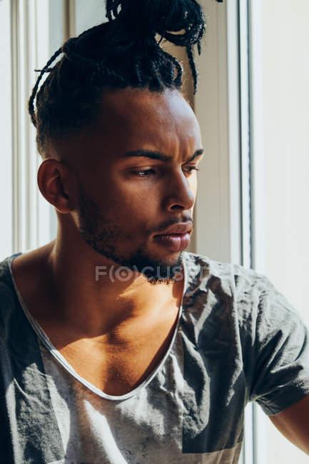 Задумчивый афроамериканец с косичками сидит дома на подоконнике — стоковое фото