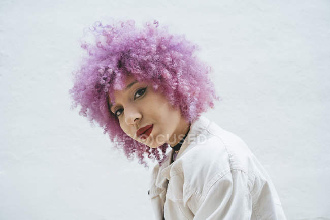 Giovane donna attraente elegante con i capelli ricci rosa uno sguardo alla fotocamera su sfondo grigio — Foto stock