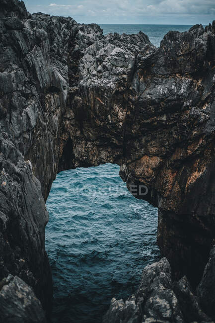 Захватывающий дух вид скалистых скал с естественной аркой и красивой лагуной в облачный день — стоковое фото