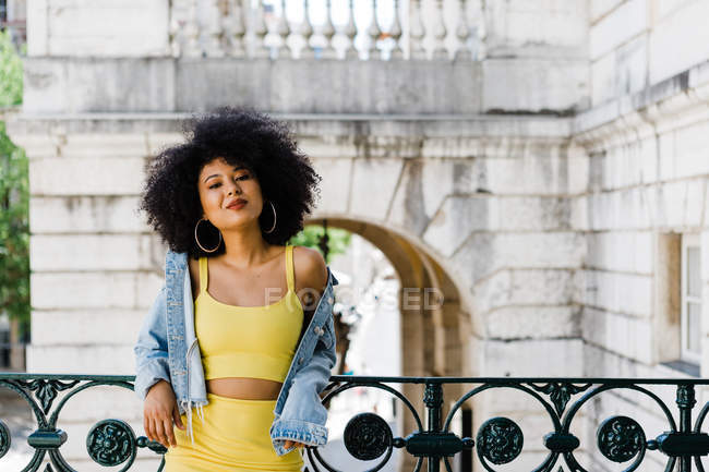 Smiling African American woman in yellow suit and denim jacket standing and looking at camera on urban background — Stock Photo