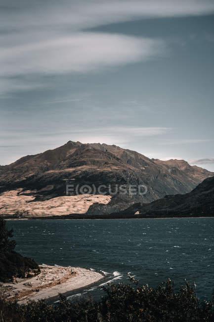 Malerischer See zwischen felsigen Bergen und majestätischem grauen Himmel an bewölkten Tagen in Lake wanaka und Lake hawea in Neuseeland — Stockfoto