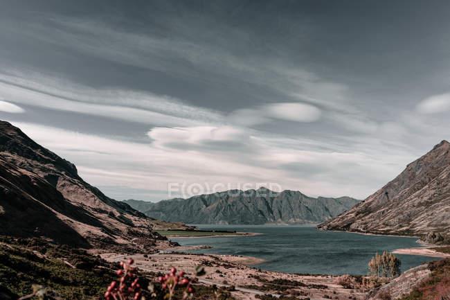 Живописное озеро между скалистыми горами и величественным серым небом в пасмурный день на озере Ванака и на озере Хавеа в Новой Зеландии — стоковое фото