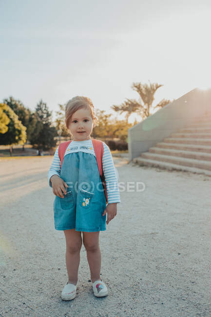 Cute little girl with backpack smiling and looking at camera while standing on sandy ground in park — Stock Photo