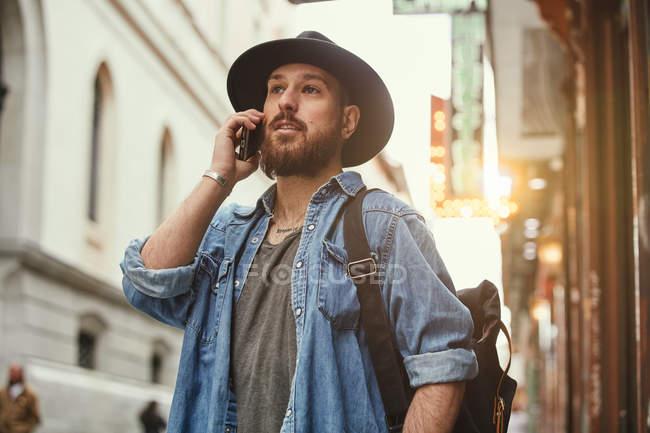 Молодой бородатый красивый мужчина в черной шляпе и джинсовой куртке весело разговаривает по мобильному телефону на улице — стоковое фото