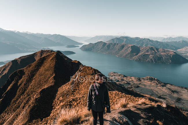 From above view of woman photographer in coat standing on high peak of mountains in range looking away — Stock Photo