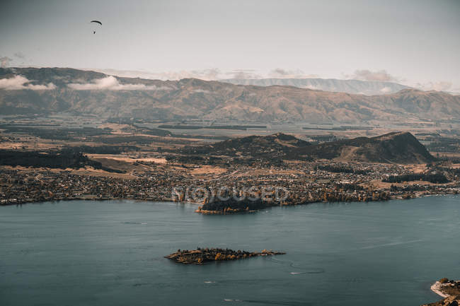 Paysage des champs verts et de la ville parmi la chaîne de montagnes sous des nuages et du parapente dans la distance — Photo de stock