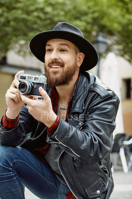 Young bearded handsome man in black hat and leather jacket taking photo in greenery street — Stock Photo