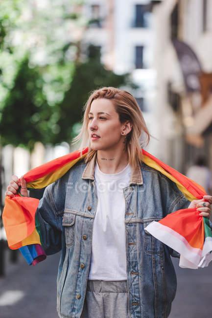 Девушка с татуировкой на лице и флагом ЛГБТ смотрит в сторону, стоя на размытом фоне городской улицы — стоковое фото