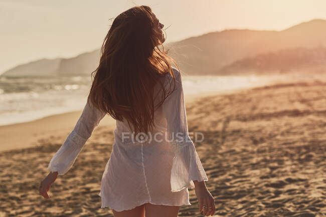 Happy brunette woman in the beach at golden hour with a white dress — Stock Photo