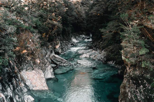 Живописное озеро между скалистыми скалами в Новой Зеландии — стоковое фото