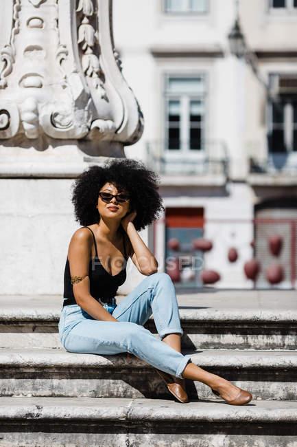 Donna etnica in jeans e canotta relax e prendere il sole su scale in pietra sullo sfondo urbano — Foto stock