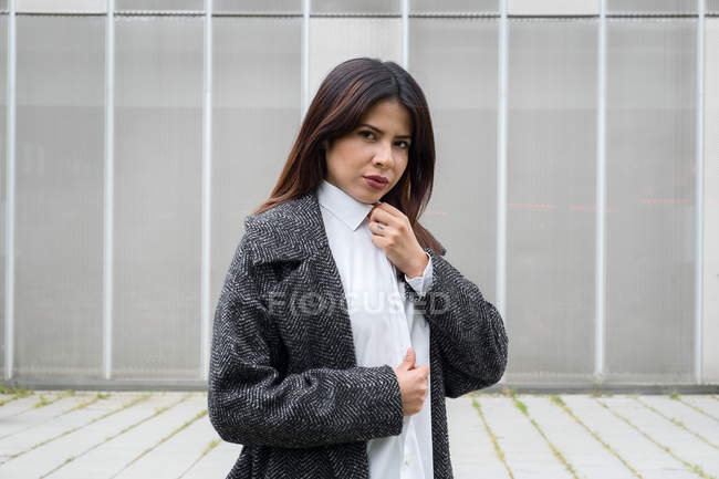 Trendy woman in coat and white shirt standing on street — Stock Photo