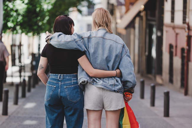 Вид сзади лесбиянок, обнимающихся и размахивающих флагами ЛГБТ во время прогулки на размытом фоне городской улицы — стоковое фото