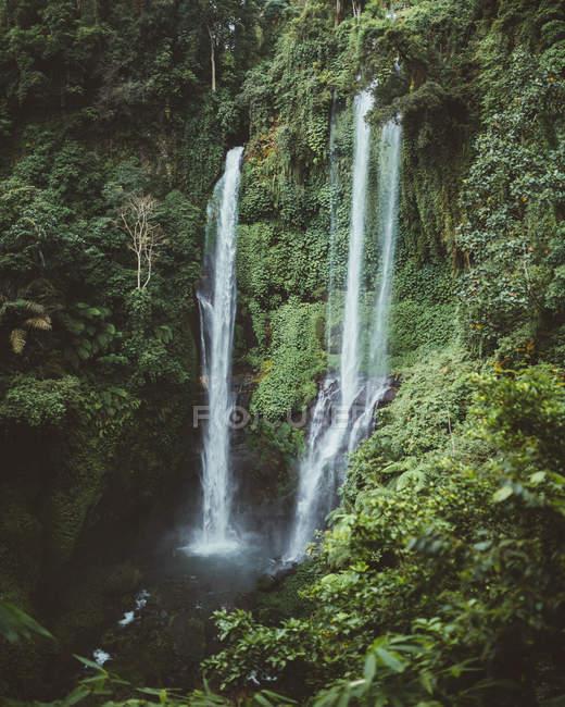 Высокие зеленые скалы с водопадом, Бали — стоковое фото