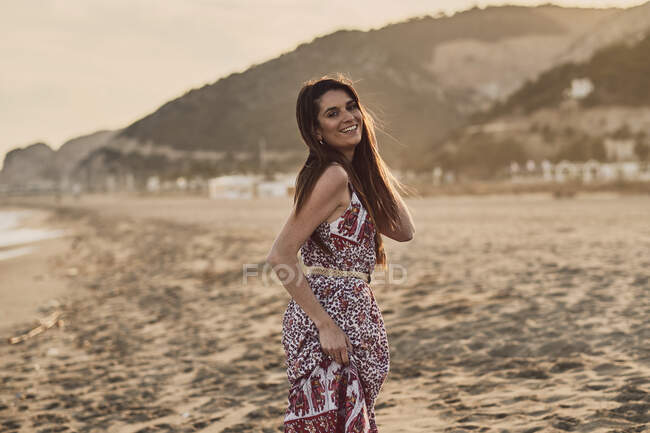 Happy brunette woman in summer dress in the beach at golden hour — стоковое фото