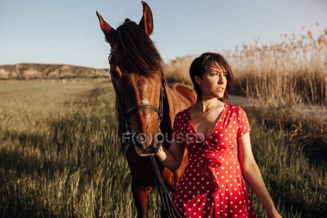 Junge Frau im langen roten Kleid mit Pferd schaut weg, während sie an einem sonnigen Tag auf dem Land auf dem Hof einer Ranch steht — Stockfoto