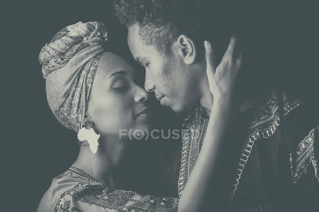 Молодая привлекательная африканская пара в яркой этнической одежде, обнимающая с закрытыми глазами — стоковое фото