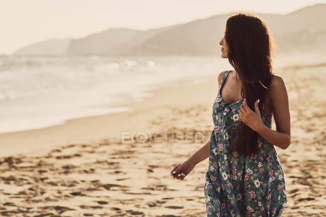 Beautiful young woman enjoying the beach at golden hour — стоковое фото