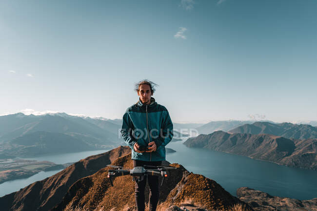 Young man controlling modern drone while standing on high peak of mountain against beautiful range landscape — Stock Photo