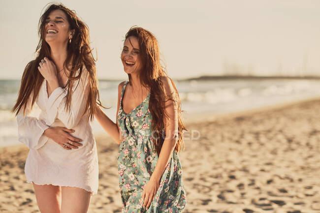 Allegro donne bruna adulte in abiti leggeri estivi sulla spiaggia di sabbia all'ora d'oro — Foto stock