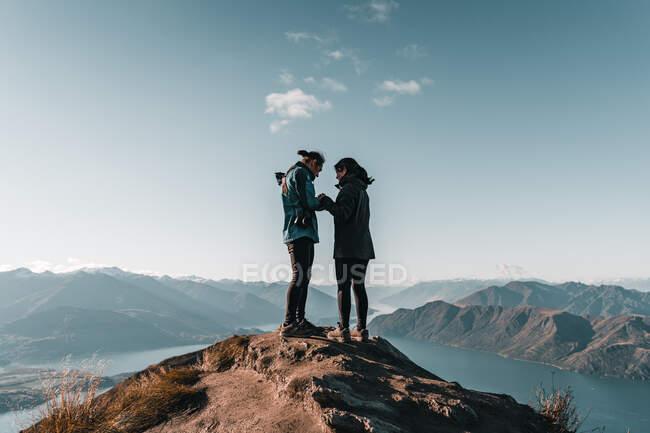 Abrazando a un par de románticos turistas felices parados en el pico de la montaña mirando el paisaje del majestuoso valle a la luz del sol - foto de stock