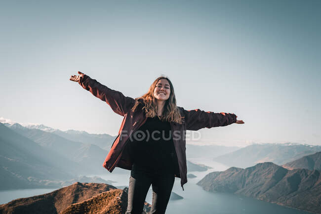 Smiling woman in coat standing on high peak of mountains in range smiling stretching arms and looking at camera — стоковое фото