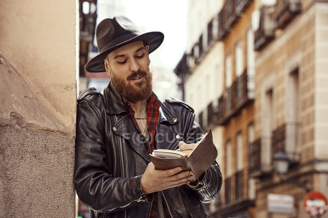 Young bearded handsome man in black hat and leather jacket with open book in hands standing near to wall in street and looking along — Stock Photo