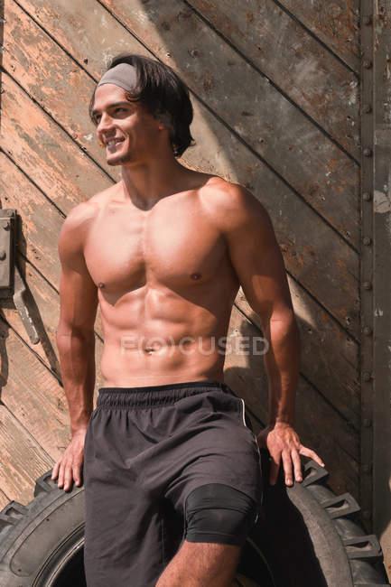 Muscular handsome muscular man posing in gym in front of wooden door — Fotografia de Stock