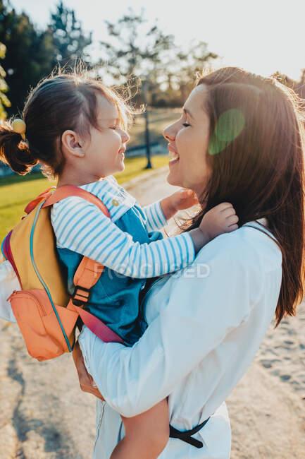 Молода жінка тримає маленьку дівчинку з рюкзаком під час перебування в парку разом у сонячний день. — стокове фото