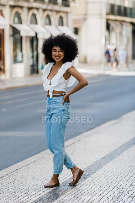 Happy ethnic woman in trendy outfit and looking at camera on summer day — Stock Photo