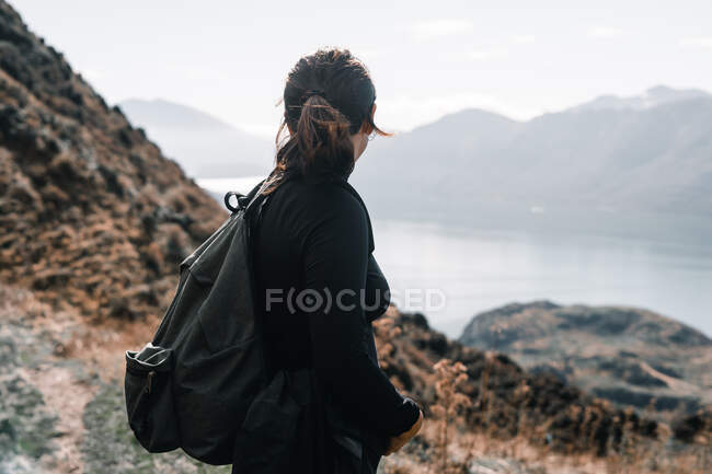 Side view of woman in black and with backpack standing on slope of mountain looking at river landscape — Stock Photo