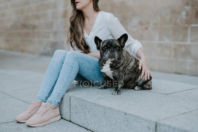 Casual jeune femme assise sur la chaussée en béton avec bulldog sur la rue — Photo de stock