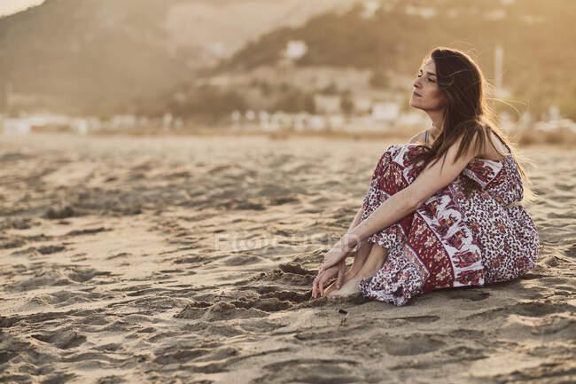 Щаслива жінка з брюнетки сидить на пляжі в золоту годину. — стокове фото