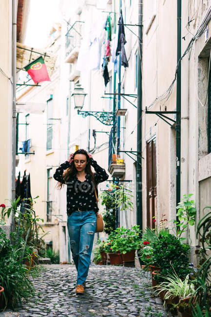 Young casual brunette walking on cobblestone street of old city — Stock Photo