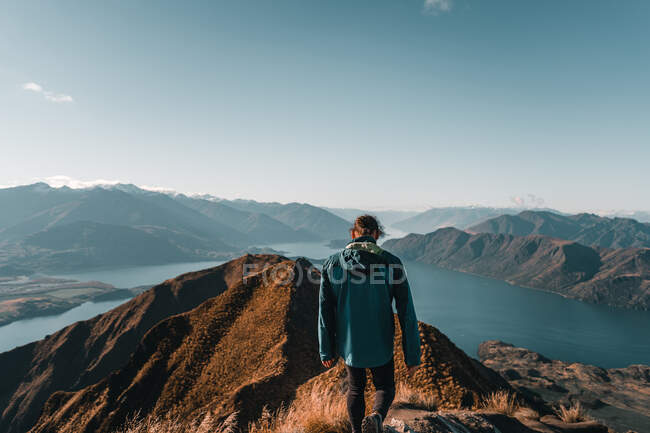 Back view of anonymous adult man in coat walking on mountain top in sunlight against majestic valley — Stock Photo