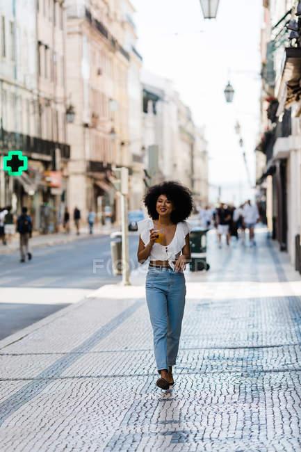 Allegro trendy donna afroamericana bere succo d'arancia su sfondo urbano — Foto stock
