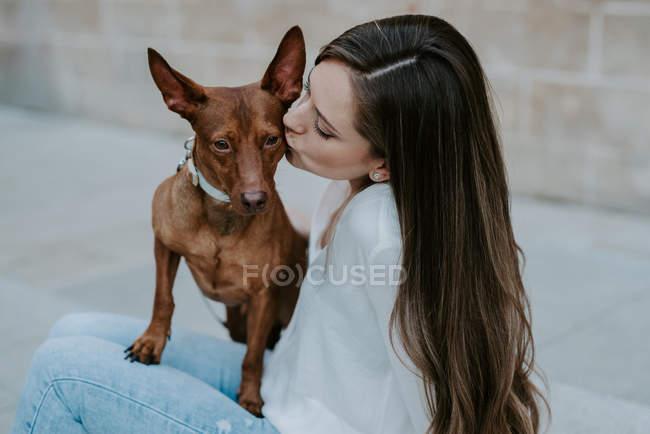 Casuale donna baciare cane segugio sulla strada — Foto stock
