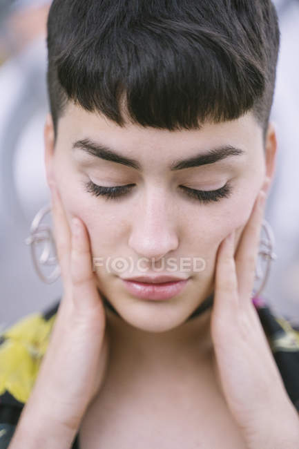 Close-up portrait of young brunette woman with closed eyes dressed in colorful shirt and black clothes — Stock Photo