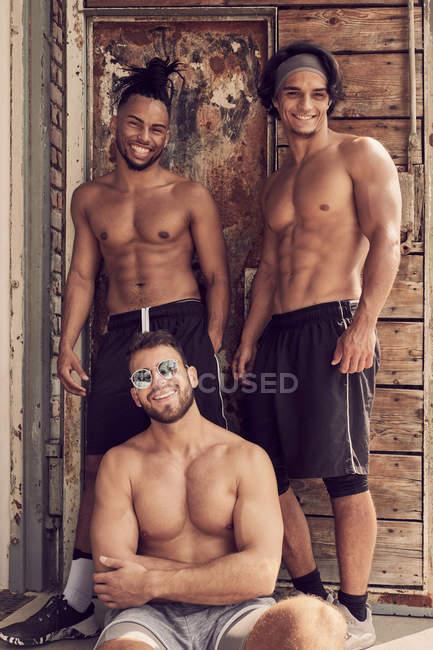 Hombres multiétnicos sin escrúpulos que se ponen y miran en la cámara cerca de la construcción poco profunda. - foto de stock