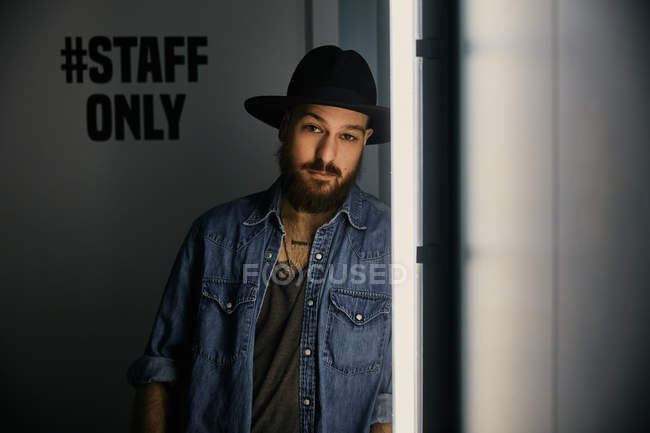 Young bearded handsome man in hat and denim shirt looking at camera in dark room — Stock Photo