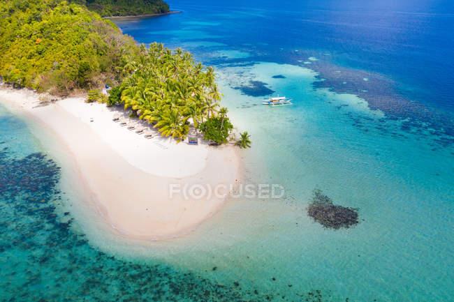 Vue aérienne de la petite île tropicale verte parmi les eaux azurées de l'océan — Photo de stock