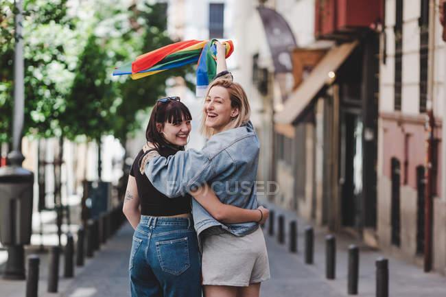 Вид сзади счастливых лесбиянок, обнимающихся и размахивающих флагом ЛГБТ во время прогулки на размытом фоне городской улицы — стоковое фото
