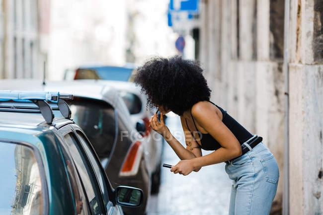 Vista lateral de la joven mujer étnica mirando a la ventana del coche y haciendo maquillaje mientras está de pie en el fondo urbano - foto de stock