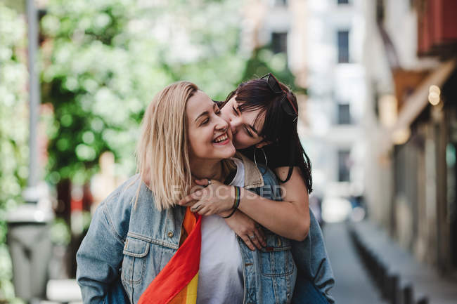 Cheerful young woman hugging and doing piggyback to smiling girlfriend while standing on pavement on blurred background of city street — Stock Photo