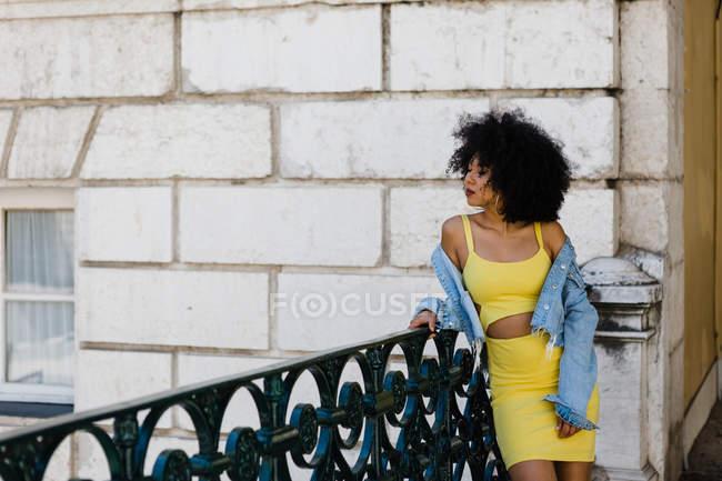 Femme afro-américaine réfléchie en costume jaune et veste en denim debout et regardant loin sur fond urbain — Photo de stock