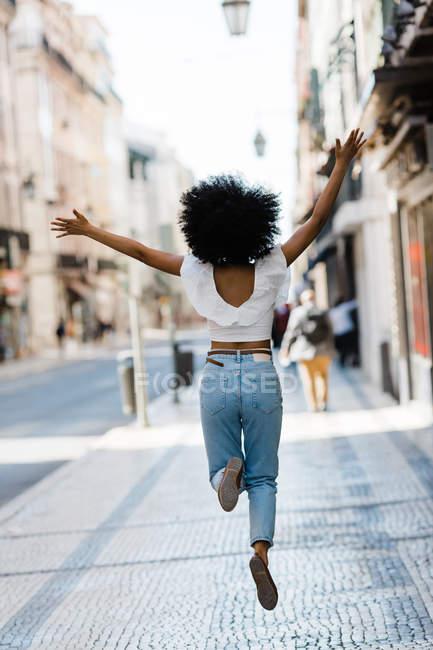 Вид сзади счастливой этнической женщины в трикотажном наряде, прыгающей от радости в летний день — стоковое фото