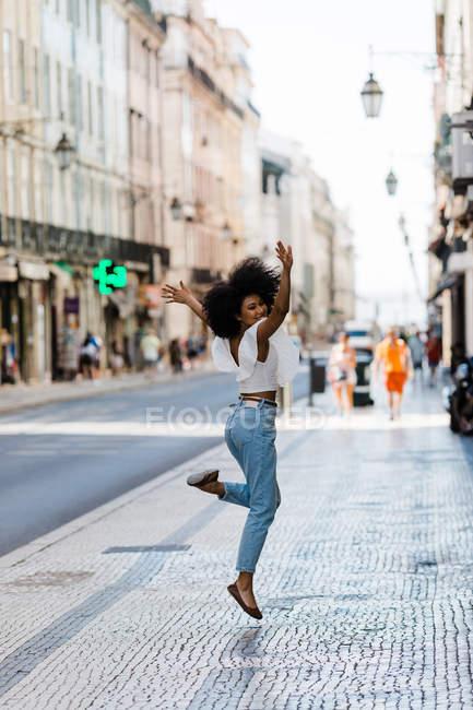 Mulher étnica feliz na roupa da moda pulando de alegria e olhando para a câmera no dia de verão — Fotografia de Stock