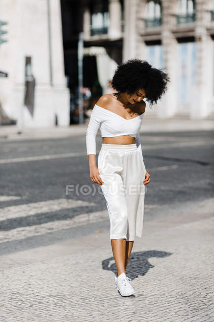 African American woman in white fashionable outfit standing on roadside against urban background — Stock Photo