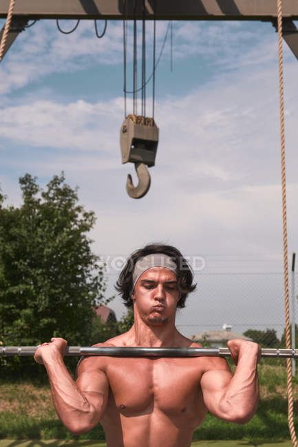 Strong handsome guy with barbell in outdoor gym — Stock Photo