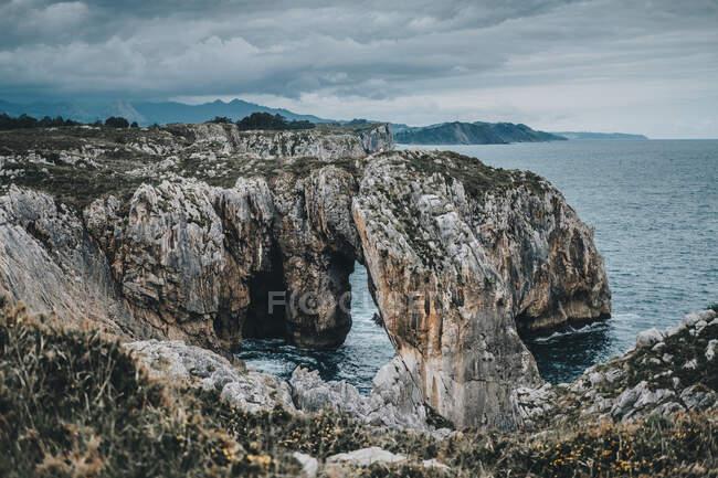 Дивовижний краєвид скелястих гір з природною аркою і гарною лагуною в похмурий день. — стокове фото